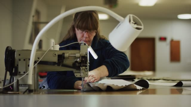 a caucasian woman in her fifties uses an industrial sewing machine on fabric in an indoor manufacturing facility - atelier fashion stock videos & royalty-free footage
