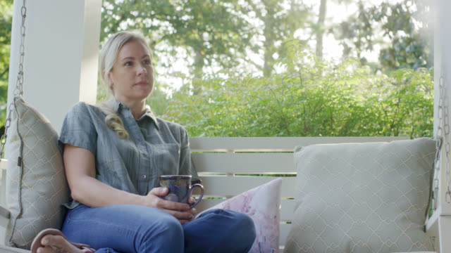 a caucasian woman in her forties drinks a cup of coffee while sitting on a porch swing outdoors surrounded by lush greenery - mug stock videos & royalty-free footage