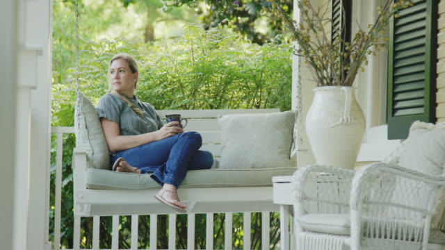 a caucasian woman in her forties drinks a cup of coffee while sitting on a porch swing outdoors surrounded by lush greenery - porch stock videos & royalty-free footage