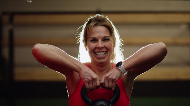 a caucasian woman in her forties wearing sports clothing lifts a kettlebell in an indoor gym while smiling and laughing - sportswear stock videos & royalty-free footage
