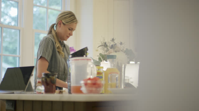 a caucasian woman in her forties works at her kitchen counter indoors - orange juice stock videos & royalty-free footage