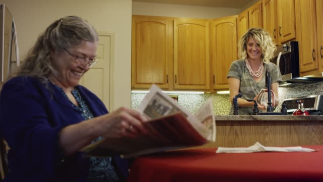 a caucasian woman in her seventies reading a newspaper at a kitchen table smiles at and talks with a caucasian woman in her thirties doing dishes at the sink - adult offspring stock videos & royalty-free footage