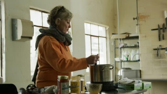 彼女の60代の白人女性は、商業台所でステンレス鋼鍋で食べ物をかき立てる - スープ点の映像素材/bロール