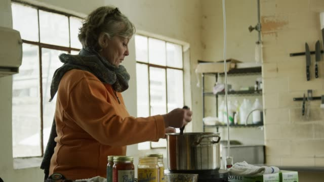 a caucasian woman in her sixties stirs food in a stainless steel saucepan in a commercial kitchen - healthcare worker stock videos & royalty-free footage