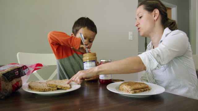 a caucasian woman in her thirties teaches her six year-old caucasian son how to make a peanut butter and jelly sandwich at a kitchen table in a domestic kitchen - making a sandwich stock videos and b-roll footage