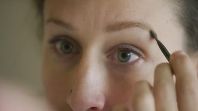 vídeos de stock, filmes e b-roll de uma mulher caucasiano em seus thirties usa uma escova pequena da composição para aplicar o pó da testa a suas sobrancelhas - joia