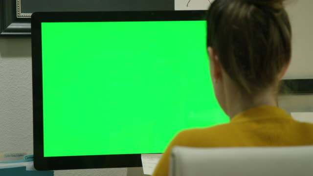 vídeos de stock e filmes b-roll de a caucasian woman in her thirties works on her computer in a home office indoors (green screen) - monitor de computador