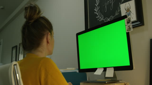 a caucasian woman in her thirties works on her computer in a home office indoors (green screen) - hairstyle stock videos and b-roll footage