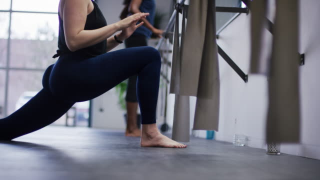 a caucasian woman in her twenties and an asian indian woman in her twenties stretch before a workout at a barre exercise studio - barre stock videos & royalty-free footage