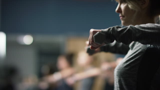 a caucasian woman in her twenties performs shoulder exercises with hand weights in an exercise class in a gym - barre fitness stock videos and b-roll footage