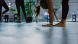 A Caucasian Woman in Her Twenties Puts Her Hands on the Floor in a Forward Bend and Then Stands Up Again in an Exercise Studio