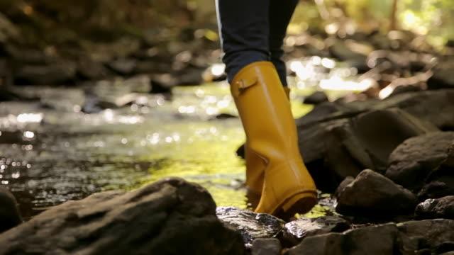 caucasian woman in rain boots walking in creek - walking in water stock videos & royalty-free footage