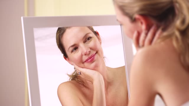 caucasian woman laughing at reflection in mirror in bathroom or bedroom - vanity stock videos & royalty-free footage