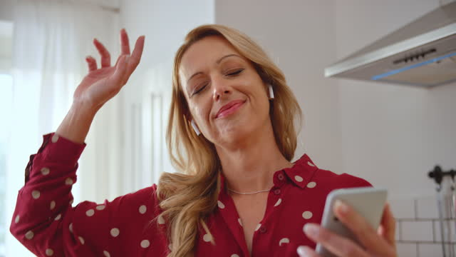 slo mo caucasian woman listening to music on her phone and dancing in her kitchen - 40 44 years stock videos & royalty-free footage