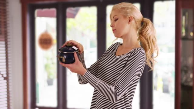caucasian woman looking at antique pot checking price tag inside store smiling - antique stock videos and b-roll footage