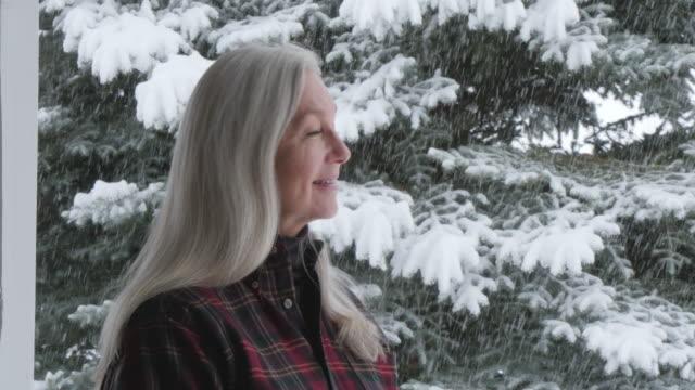 vídeos y material grabado en eventos de stock de caucasian woman on porch watching snow - camisa a cuadros