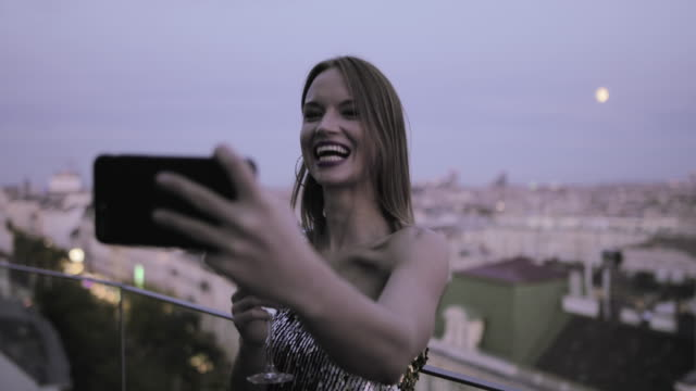 caucasian woman on rooftop taking selfie at sunset in cocktail dress - cocktail dress stock videos & royalty-free footage