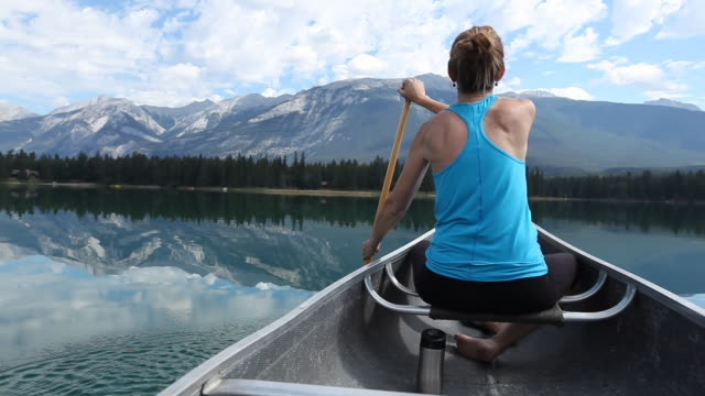 caucasian woman paddling in canoe, jasper, alberta, canada - oar stock videos & royalty-free footage