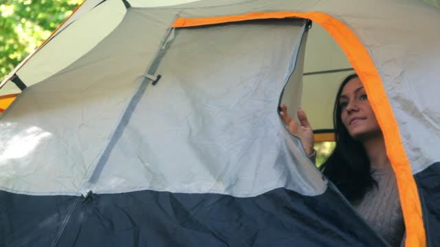 Caucasian woman peeking out from unzipped tent
