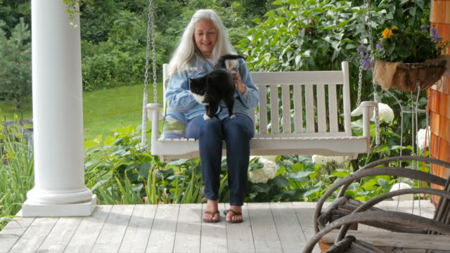 Caucasian woman petting cat on patio