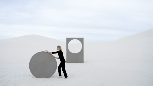 caucasian woman rolls circular portal in desert, medium shot - full length stock videos & royalty-free footage