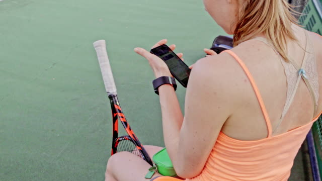 Caucasian woman sitting at tennis court text messaging on cell phone