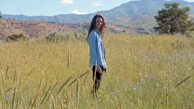caucasian woman standing in field of tall grass - weitwinkelaufnahme stock-videos und b-roll-filmmaterial