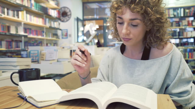 caucasian woman studying in a library. - esame video stock e b–roll