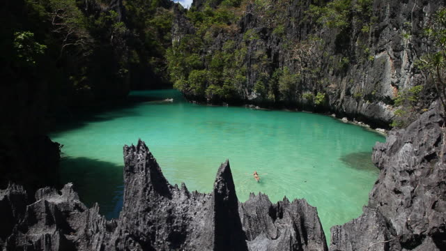 ws of caucasian woman swimming in idyllic tropical inlet surrounded limestone cliffs / small lagoon, miniloc island, bacuit archipelago, el nido, palawan, philippines - arcipelago video stock e b–roll