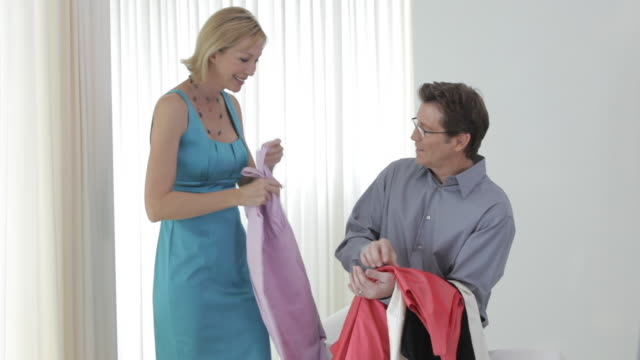 Caucasian woman trying on dress, husband watching