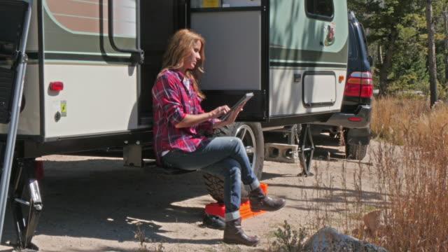 caucasian woman using digital tablet at trailer - wohnmobil stock-videos und b-roll-filmmaterial