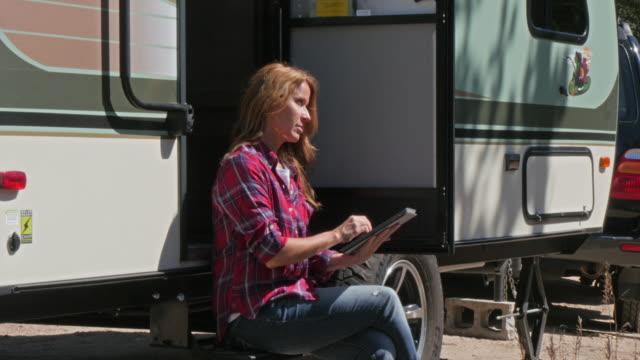 vídeos de stock, filmes e b-roll de caucasian woman using digital tablet at trailer - vão de porta