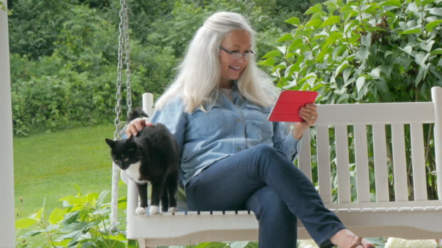 Caucasian woman using digital tablet on swing
