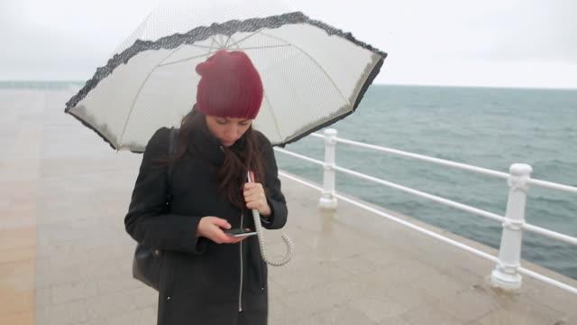 Europäischer Abstammung Frau zu Fuß am Strand und mit Ihrem Smartphone.