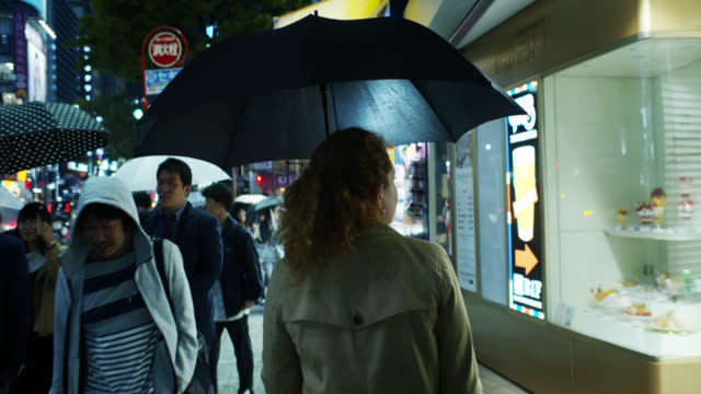 caucasian woman walking through tokyo on rainy night - 市街地の道路点の映像素材/bロール