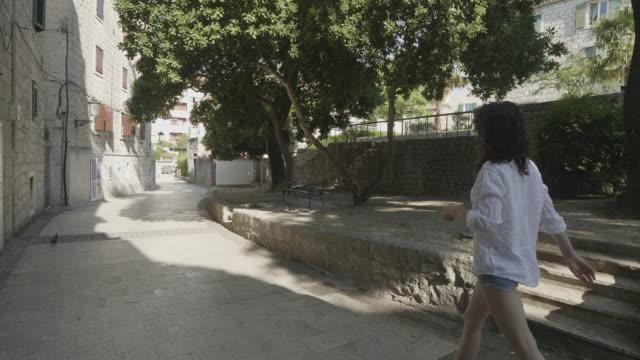 vídeos y material grabado en eventos de stock de caucasian woman walks down empty street in hvar, croatia - cultura croata