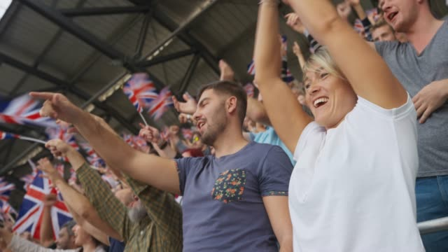 caucasian woman waving her hands in the air and cheering on the stadium tribune while holding the union jack flag - british culture stock videos & royalty-free footage