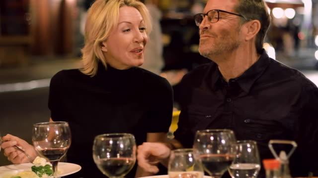 vídeos de stock, filmes e b-roll de caucasian woman wiping food from shirt of husband in restaurant - garfo