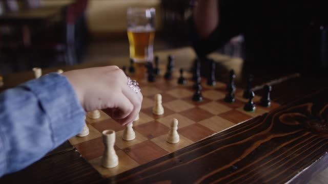 A Caucasian Woman with a Ring Moves Her Pawn Forward in a Chess Game at a Bar