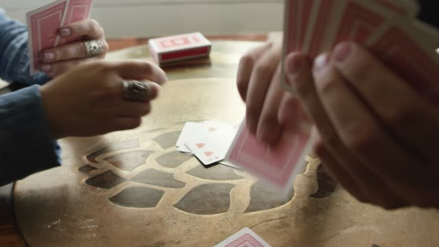 a caucasian woman with a ring on plays a card game with a caucasian male opponent - carte da gioco video stock e b–roll