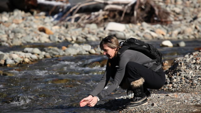 Caucasian woman with backpack drinking from creek