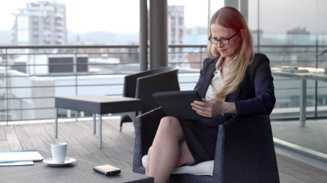 caucasian woman with glasses smiling while using her digital tablet in a lounge on a rooftop terrace in the city - blonde hair stock videos & royalty-free footage