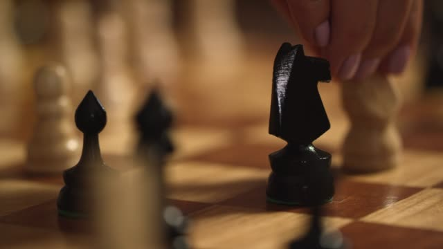 A Caucasian Woman with Pink Fingernail Polish Removes Her Opponent's Knight from the Board in a Game of Chess