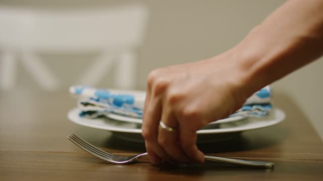 a caucasian woman's hand places a fork to the left of a white dinner plate with a white salad plate and a colorful, floral cloth napkin on a wooden table - place setting stock videos & royalty-free footage