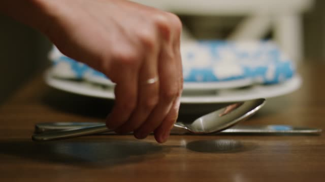 a caucasian woman's hand places a spoon next to a table knife of a place setting on a wooden table - putting stock videos & royalty-free footage