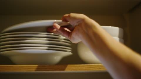 白人の女性の手は、開いたキッチンの食器棚に様々なサイズのクリーンボウルを配置し、ドアを閉じます - ハイチ点の映像素材/bロール