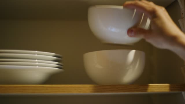 a caucasian woman's hand places clean bowls of various sizes into an open kitchen cupboard then closes the door - chores stock videos & royalty-free footage