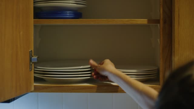 a caucasian woman's hand places clean plates of various sizes into an open kitchen cupboard - crockery stock videos & royalty-free footage