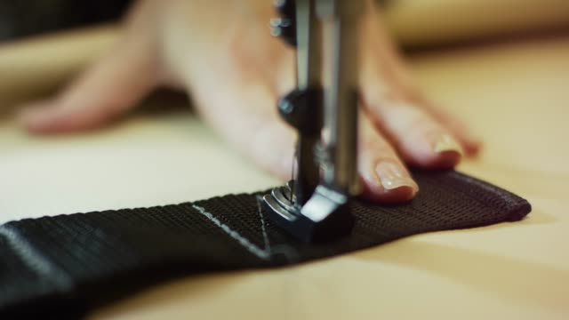 a caucasian woman's hands guide an industrial sewing machine's presser foot as it sews a nylon strap in an indoor manufacturing facility - needle plant part stock videos & royalty-free footage