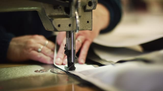 a caucasian woman's hands guide an industrial sewing machine's presser foot as it sews fabric in an indoor manufacturing facility - atelier fashion stock videos & royalty-free footage